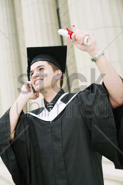 graduate talking on the phone while holding up his scroll stock photo
