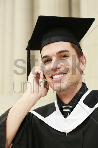 graduate talking on the phone stock photo