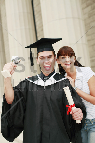 graduate with trophy and scroll posing with woman stock photo