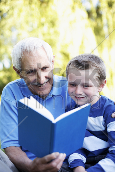 grandfather and grandson sharing a book stock photo
