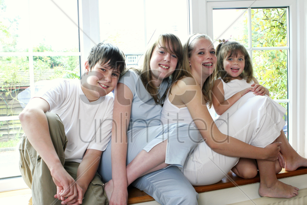 group shot of boy and girls sitting by the window stock photo