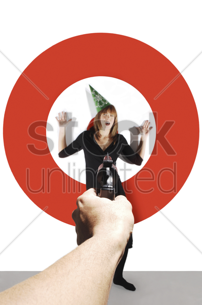hand aiming a pistol at a businesswoman with party hat stock photo