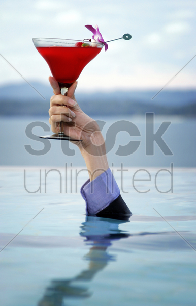 hand coming out from the water holding a glass of cocktail stock photo