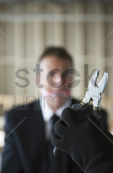 hand holding pliers with gagged businessman looking at it stock photo