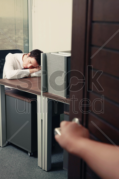 hand opening door, revealing businessman sleeping in his room stock photo