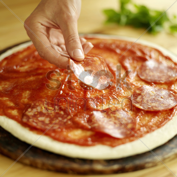 hand placing mozzarella cheese slice on raw pizza base with basil in background stock photo
