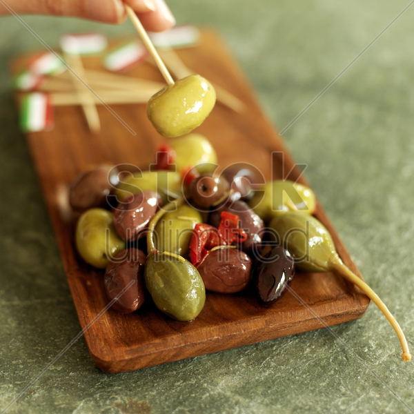 hand taking fresh italian olive with italian flag pick from wooden plate stock photo