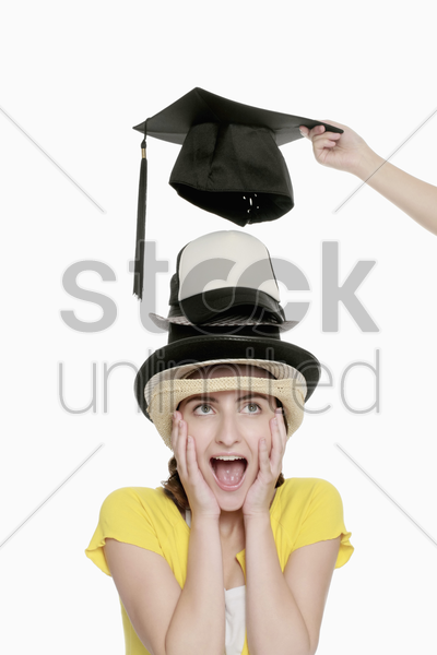 hand taking mortarboard away from woman's head, woman screaming stock photo