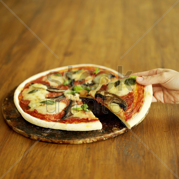 hand taking slice of freshly cooked pizza with mushroom stock photo