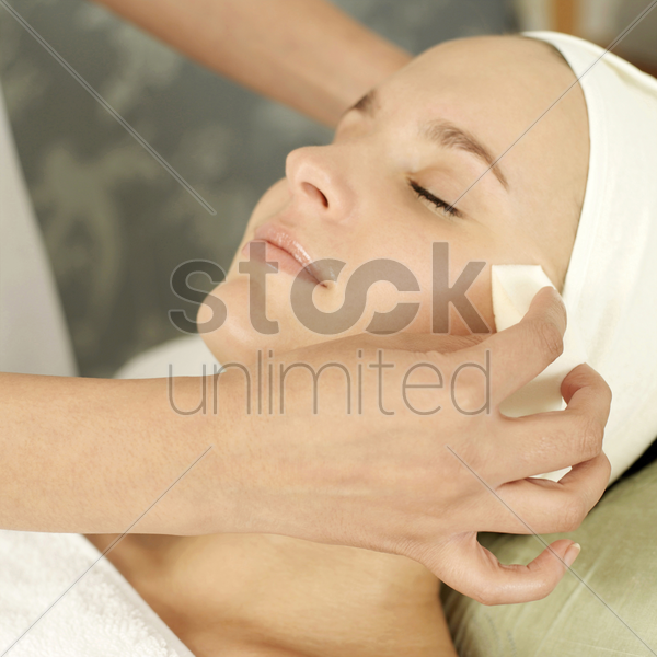 hand wiping woman's face with cleansing cotton stock photo