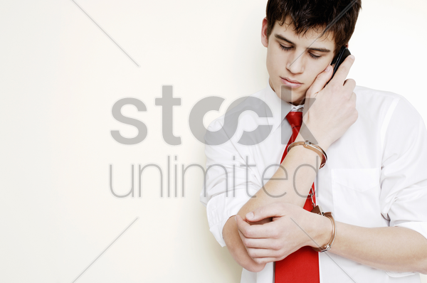 handcuffed businessman talking on the cell phone stock photo