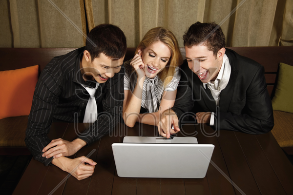 happy business people looking at laptop stock photo