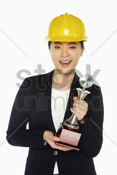 happy female architect holding up a trophy stock photo