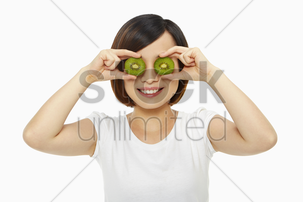happy woman covering her eyes with a kiwi stock photo