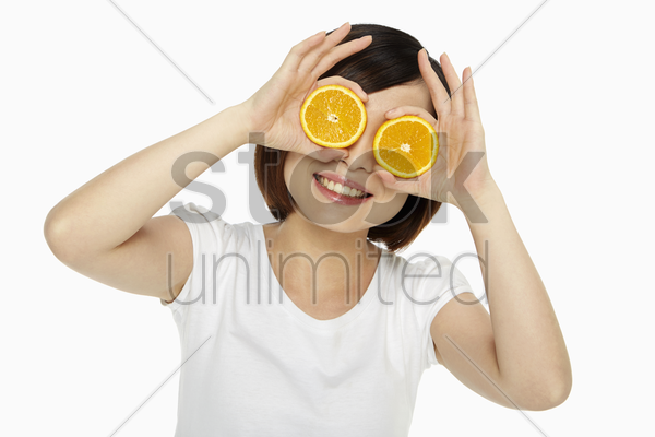 happy woman covering her eyes with an orange stock photo