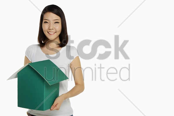 happy woman holding a cardboard house stock photo