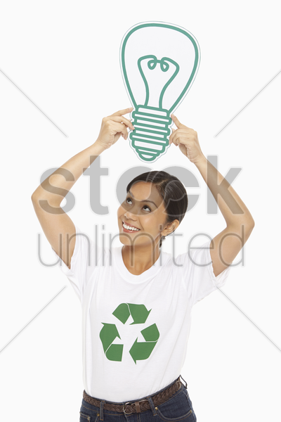 happy woman holding up a cardboard light bulb stock photo