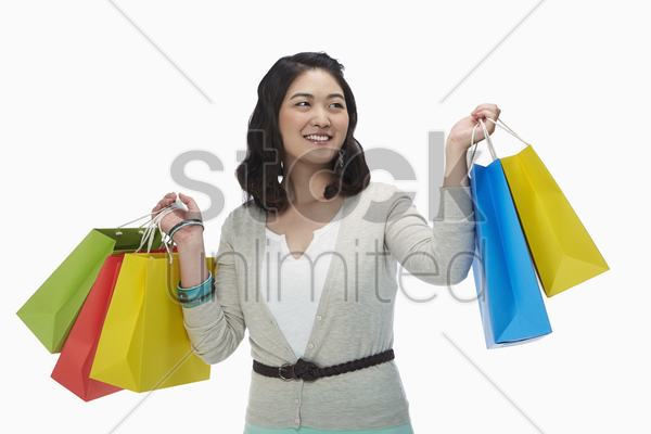 happy woman holding up colorful paper bags stock photo