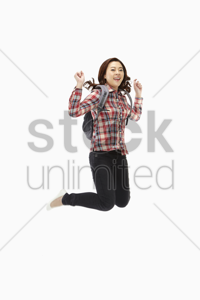 happy woman jumping mid air stock photo
