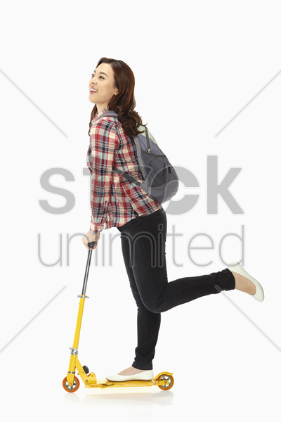 happy woman riding on a scooter stock photo