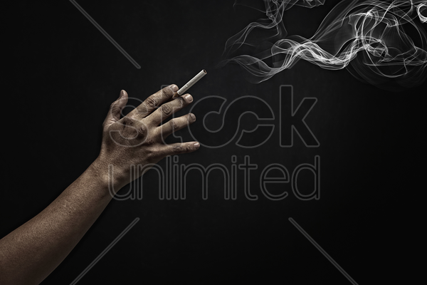 human hand holding a burning cigarette stock photo