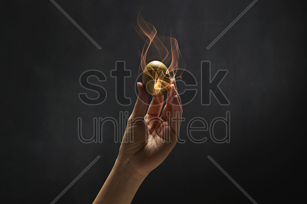 human hand holding a golden egg stock photo