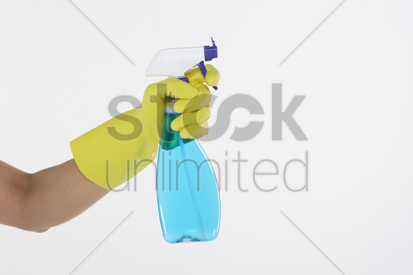 human hand holding a spray bottle stock photo