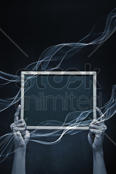 human hand holding up a blank blackboard stock photo
