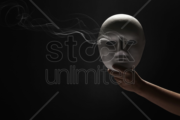 human hand holding up a face mask stock photo