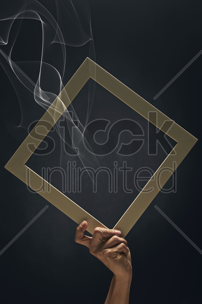 human hand holding up a picture frame stock photo