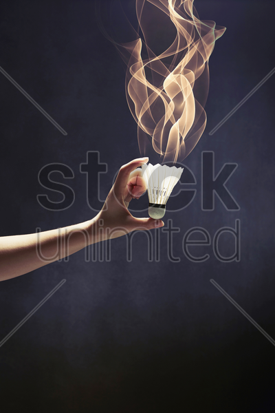 human hand holding up a shuttlecock stock photo