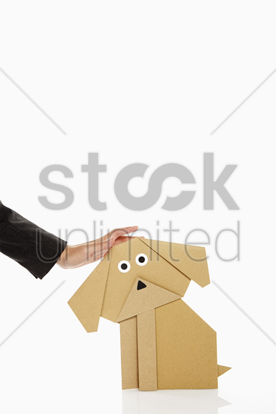 human hand petting a paper dog stock photo