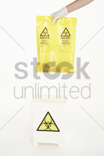 human hands disposing biohazard waste stock photo