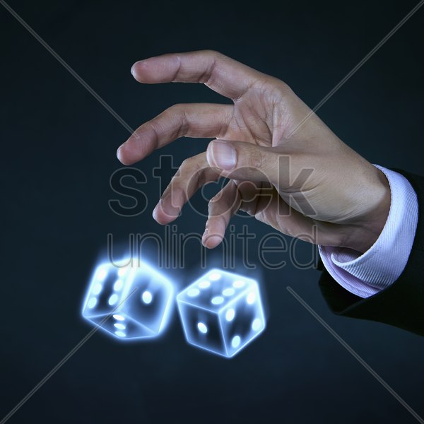 human hands tossing dice stock photo