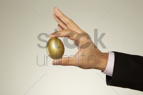 human holding up a golden egg stock photo