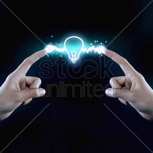 illuminated light bulb in the middle of two fingers stock photo