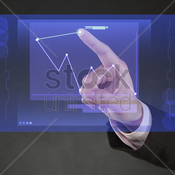index finger pointing at a digital graph chart stock photo