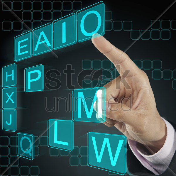 index finger pointing at alphabet tiles stock photo