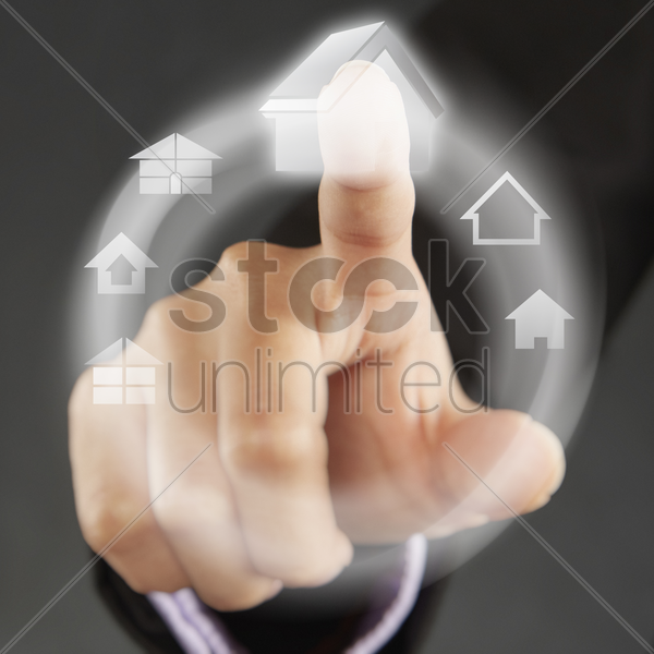 index finger pointing at home symbols on a touch screen menu stock photo