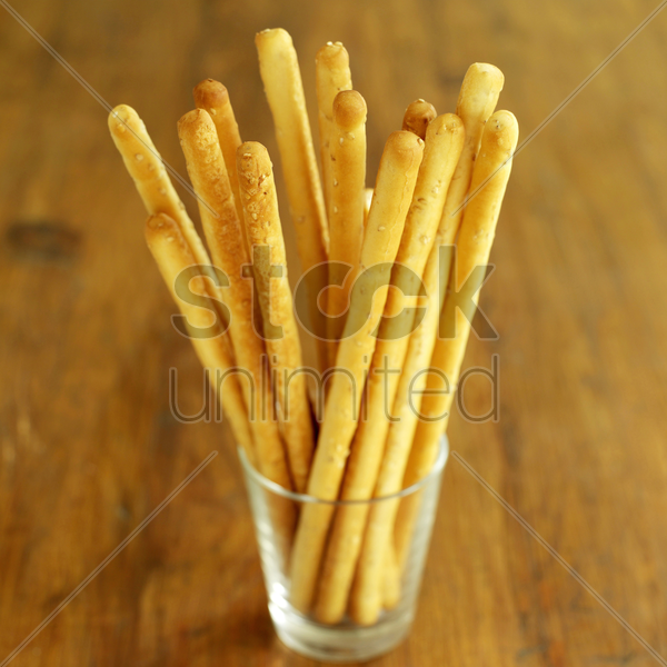 italian breadsticks in glass on wooden table stock photo