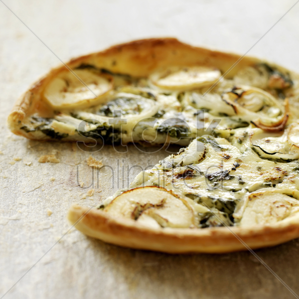 italian goat cheese and spinach quiche with slice missing stock photo