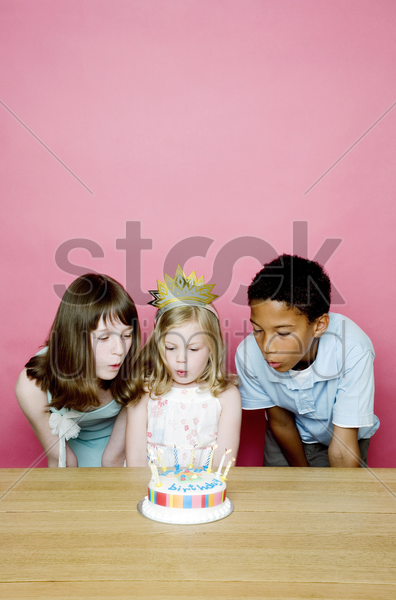 kids blowing the candles on the birthday cake stock photo