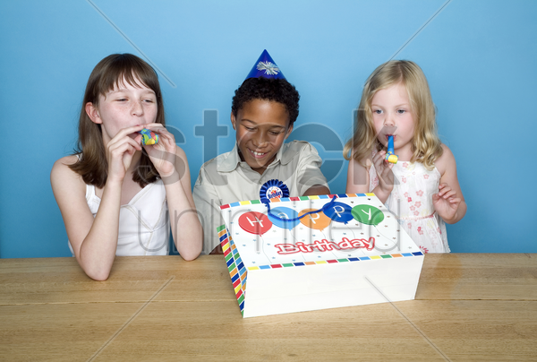 kids playing with party blowers stock photo