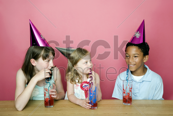 kids with party hats drinking stock photo