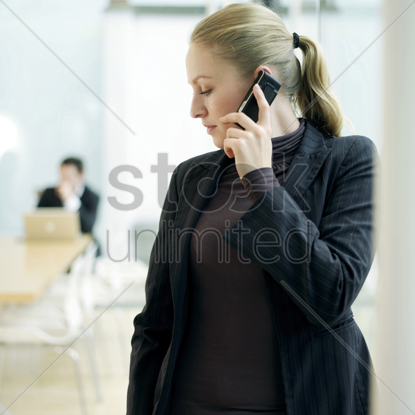 lady using cell phone, a guy sitting at the back stock photo