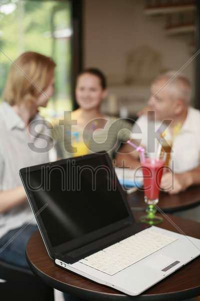 laptop on the table, men and woman in the background stock photo