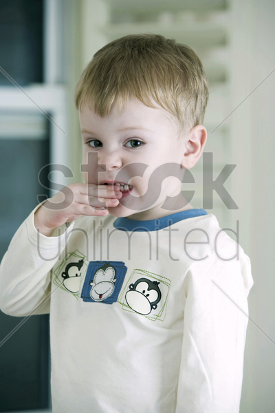 little boy biting his hand stock photo