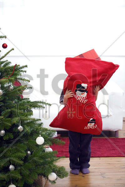 little boy hugging a bag full of gifts stock photo