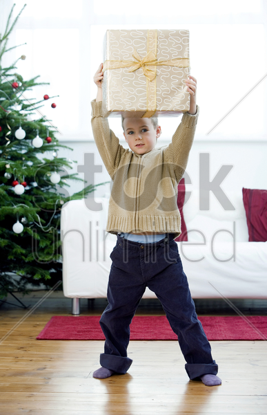 little boy lifting a present stock photo