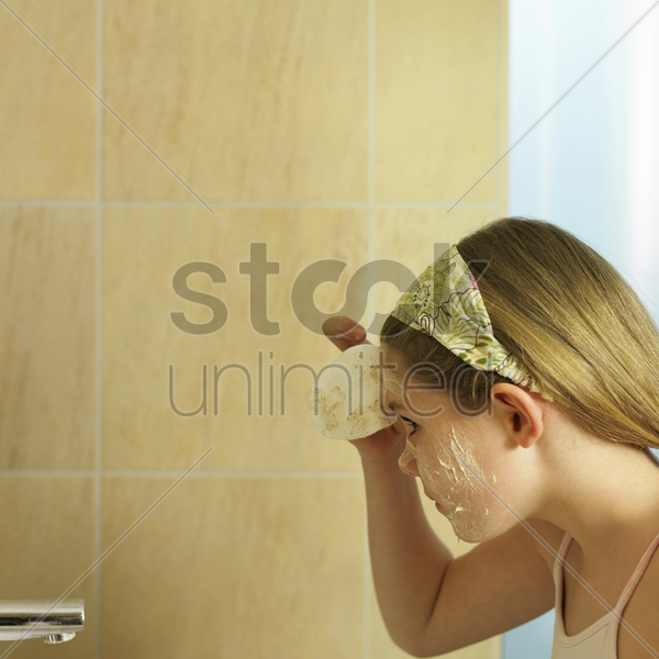 little girl doing facial in bathroom stock photo